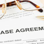 Glasses and a pen on top of a lease agreement